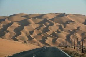 On the edge of the Empty Quarter, dunes rippling down to the road...
