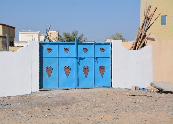 1-Omani village, traditional doors in the courtyard wall, against the desert background colours, the blue makes an instant pop of colour...