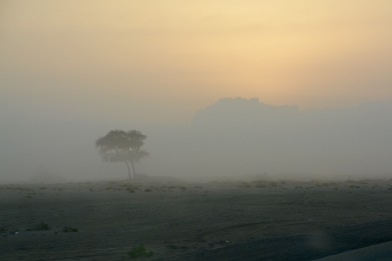 Sunrise behind the clouds, the lonely sabkha wastes of Ash Sharquiyah...