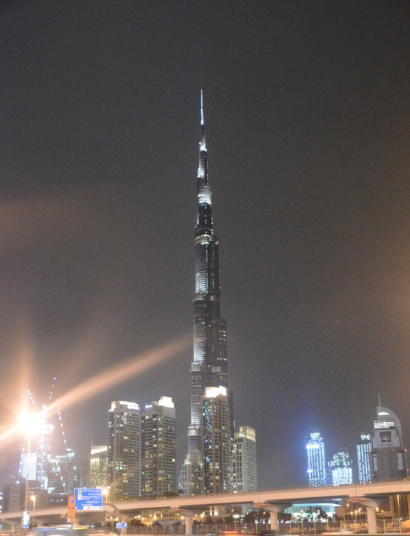 At night Burj Khalifa is lit up high above the city....