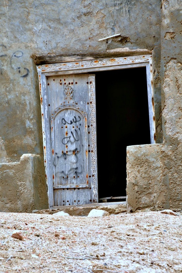 A crooked door with Arabic inscription carved into the lintel...